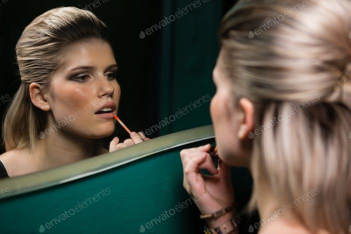 Woman applying lips gloss while looking at mirror