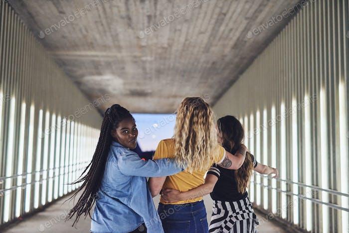 Lachende junge Freundinnen zu Fuß in der Stadt in der Nacht