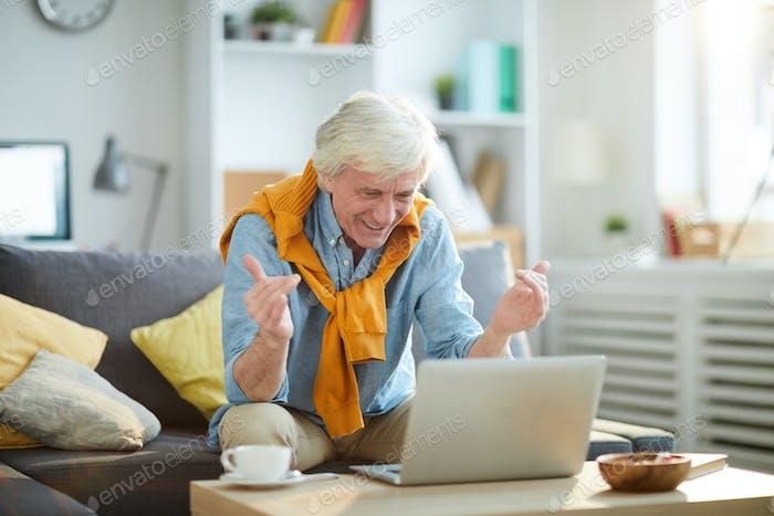 Excited Senior Man Using Laptop