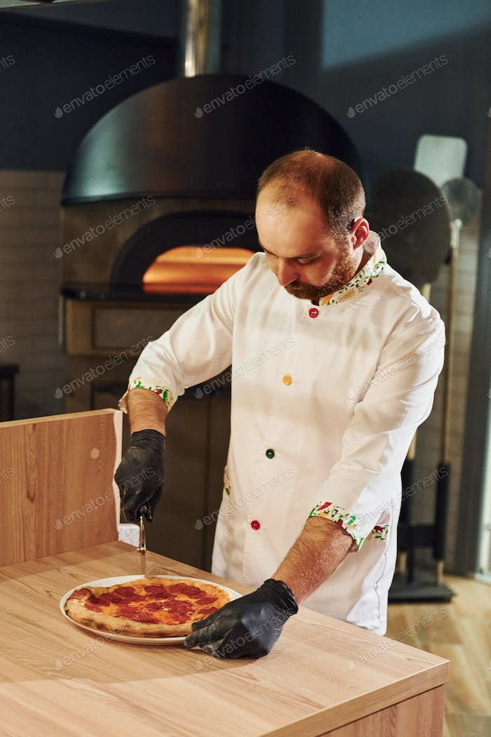 Chef in white clothes preparing delicious pizza on the kitchen of restaurant