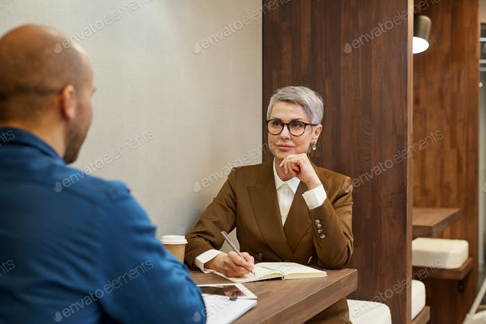 Mature Businesswoman Meeting Client in Cafe