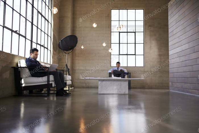 Two men sitting in the foyer of a business building