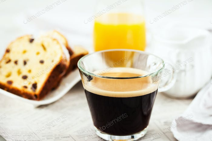 Continental breakfast table with cup of hot black coffee, milk,