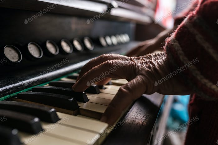 Old man playing the piano in a close up view of his wrinkled han