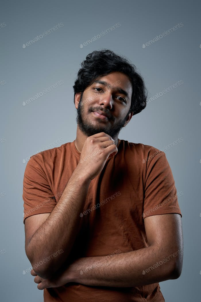 Froh, hindu mit modernen Haristyle-Posen im Studio, die in die Kamera schauen