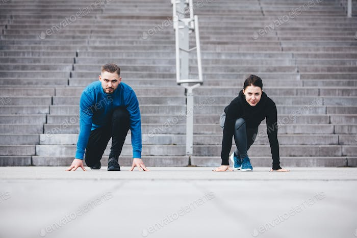 Young athletic couple in a steady position crouching.