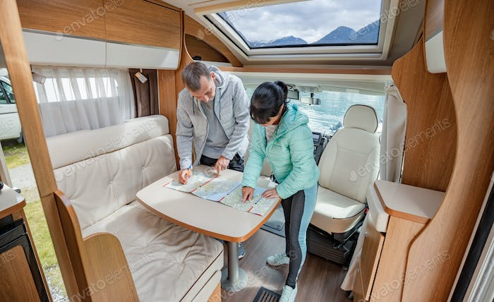 Couples in RV Camper looking at the local map for the trip.