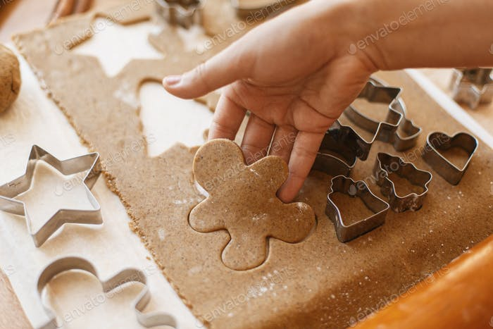 Hand cutting gingerbread dough in christmas man shape. Christmas holiday tradition