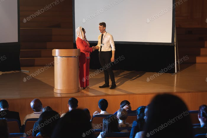 Business colleague handshaking each other in front of the audience in auditorium