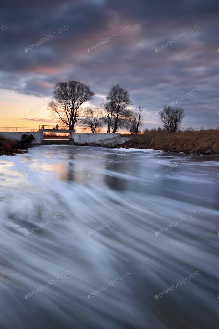 Fast river in cloudy sunrise