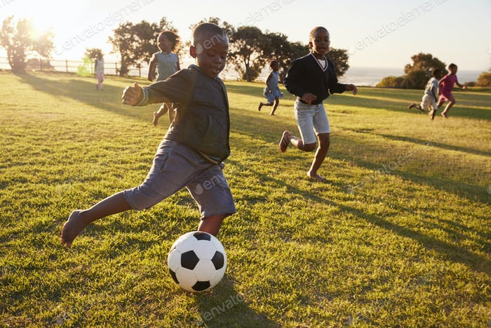 Elementary school kids playing football in a field