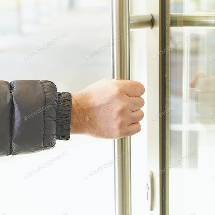 Man takes door handle with his hand and opens door. Place of accumulation of coronavirus, COVID-19