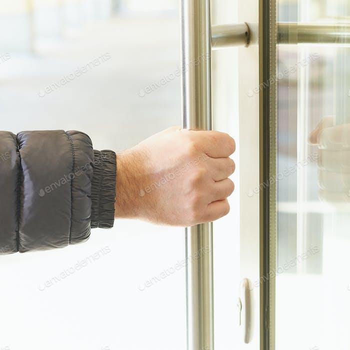 El hombre toma la manija de la puerta con la mano y abre la puerta. Lugar de acumulación koronavirus, COVID-19