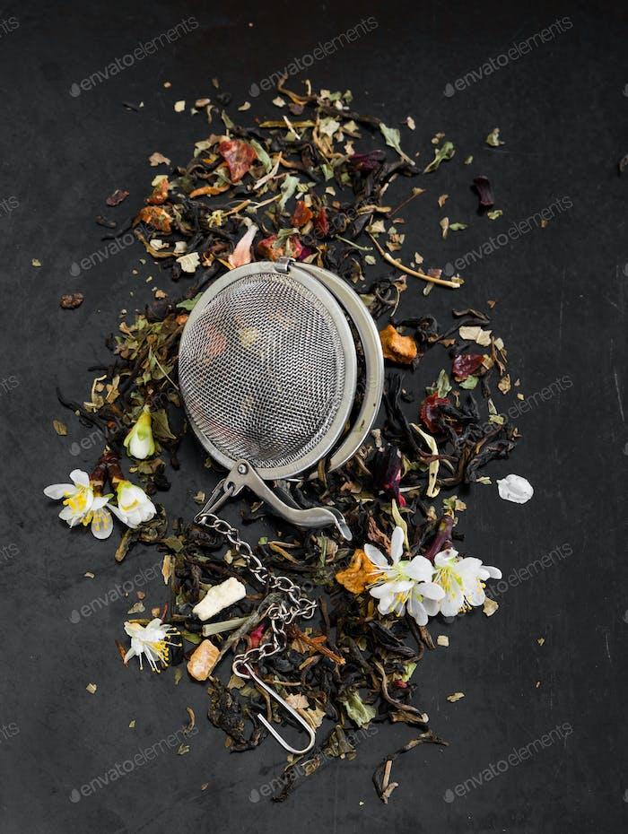Kräutertee im Teesieb auf schwarzem rustikalem Hintergrund.