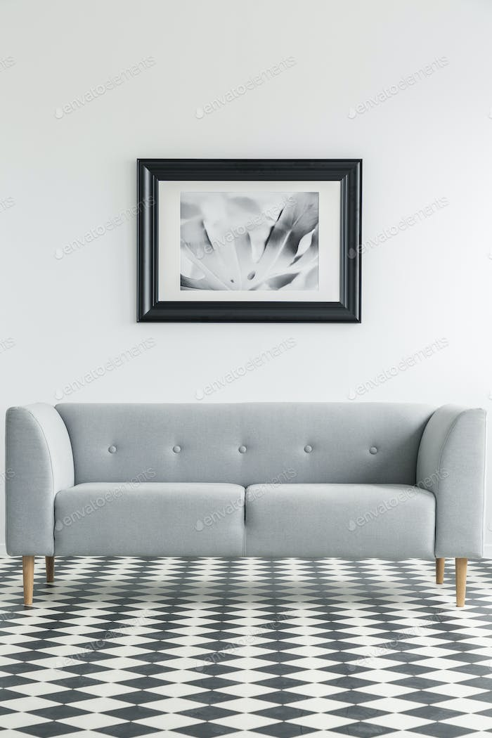 Simple, grey sofa on a checkered floor with a poster in the back