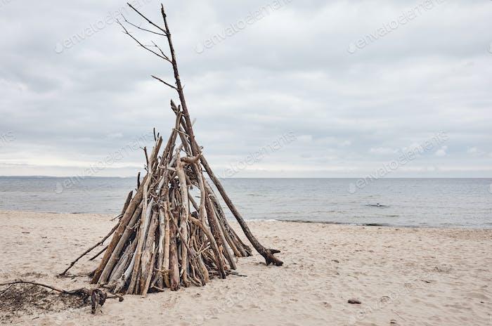 Temporary wood shelter on an empty beach.