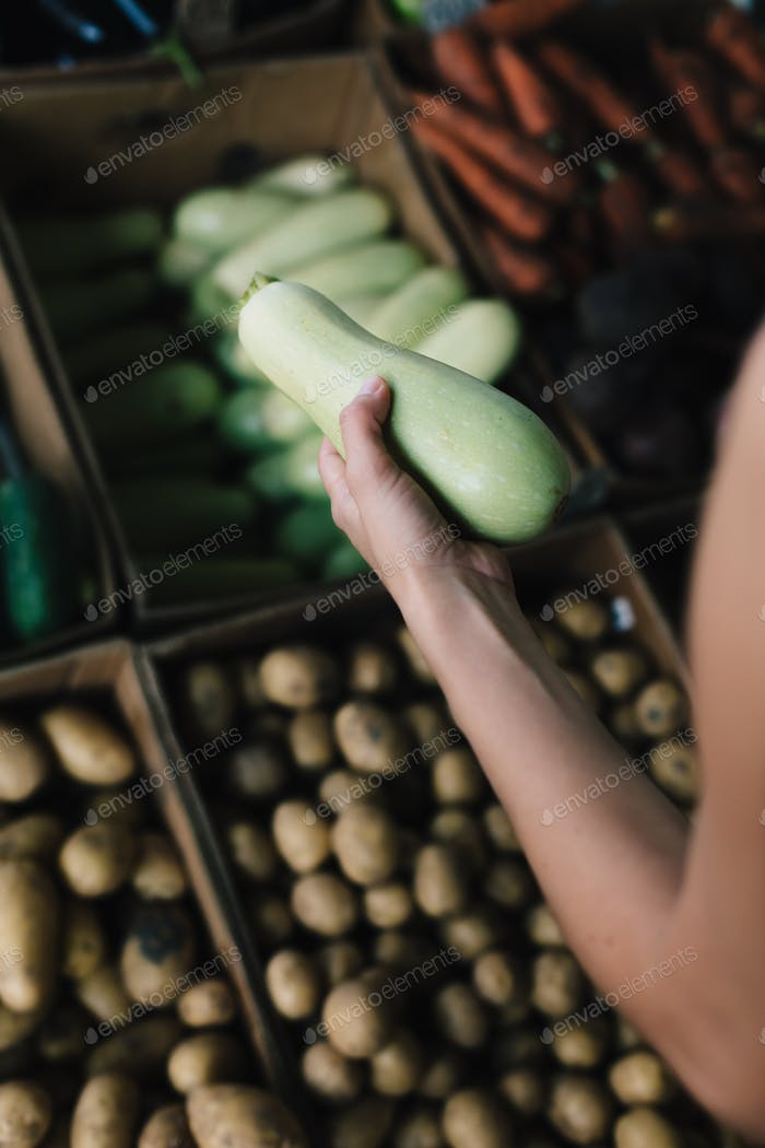 Crop person buying vegetables