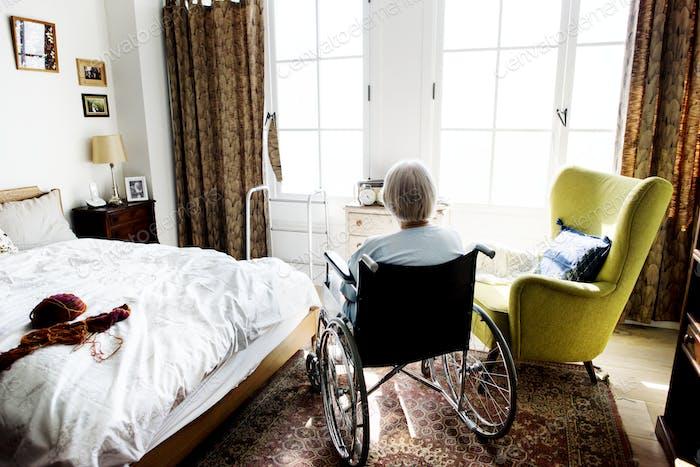 Senior Frau sitzt auf dem Rollstuhl allein