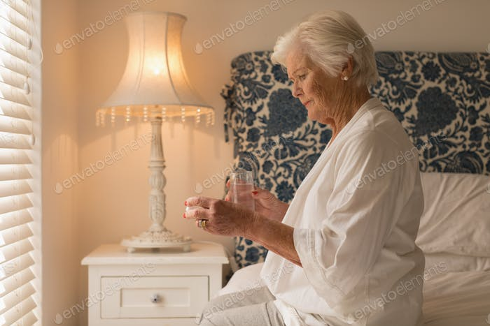 Side view of a senior woman having medicine with a glass of water in her bedroom at home