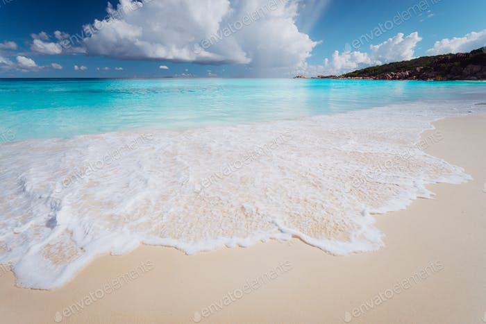 Amazing water colors of Grande Anse, La Digue Island Seychelles. Sea foam on Tropical beach with