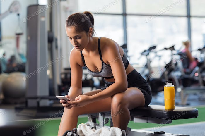 Woman using phone at gym