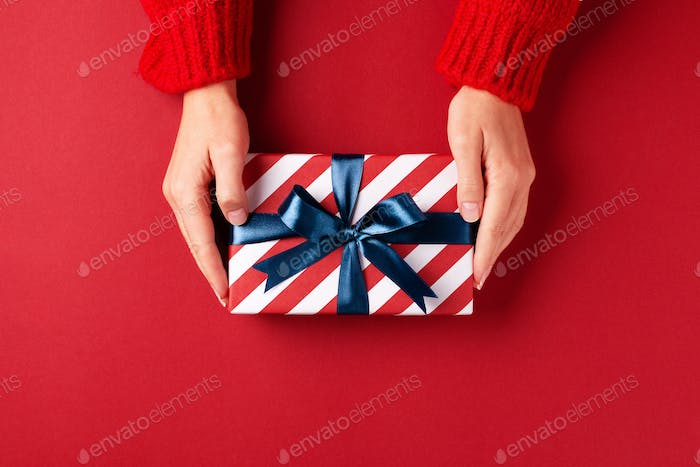 Female`s Hand in Red Pullover Holding Gift Box.