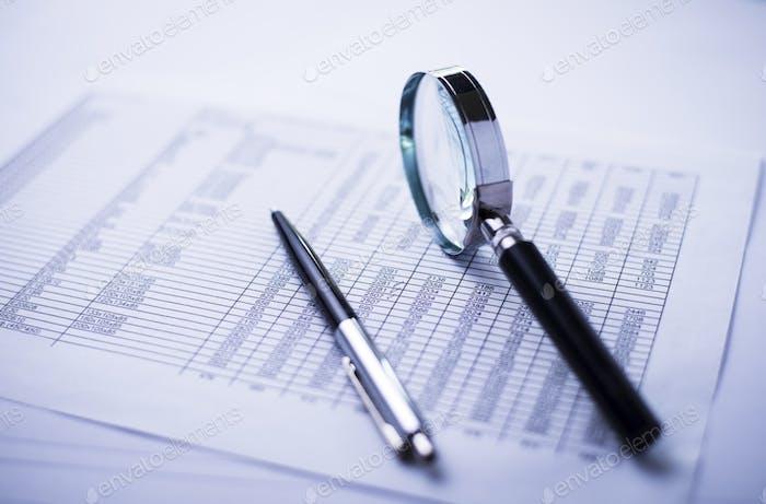 Dinero, pluma, lupa y el informe financiero