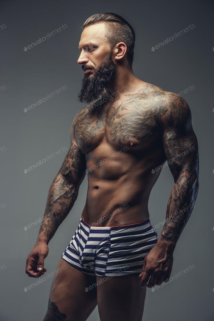 Naked bearded man with tattooed body.