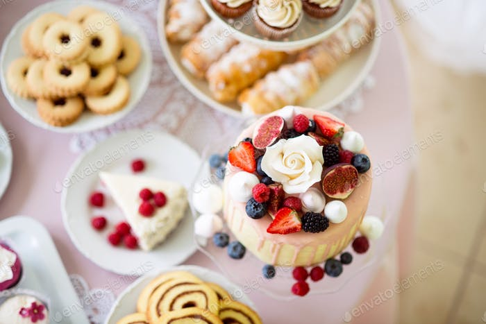 Cake with various berries and meringues on a stand.