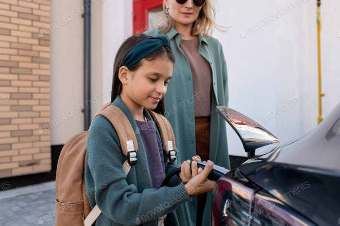 Little girl with backpack helping her mother charge ev car battery