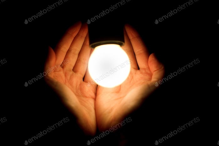 light bulb in humans hands on black background, energy saving and innovation concept