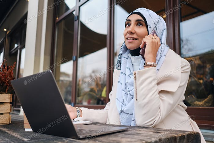 Young attractive Arabic businesswoman in hijab talking on smartphone during work on laptop on street