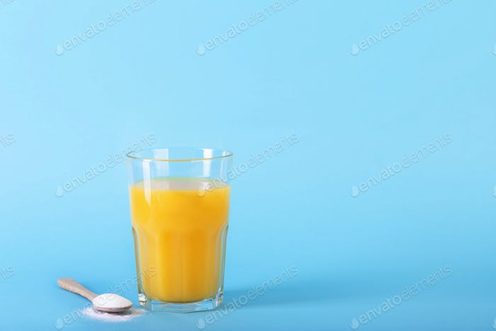 A glass juice and a spoon with collagen powder on blue background.