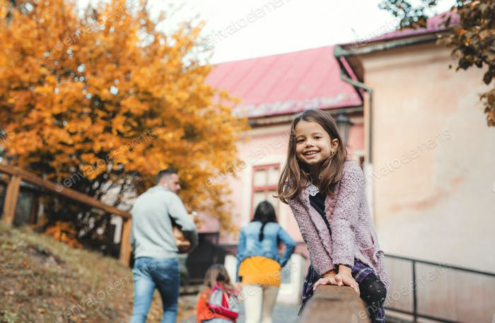 A portrait of small girl with her family in town in autumn.