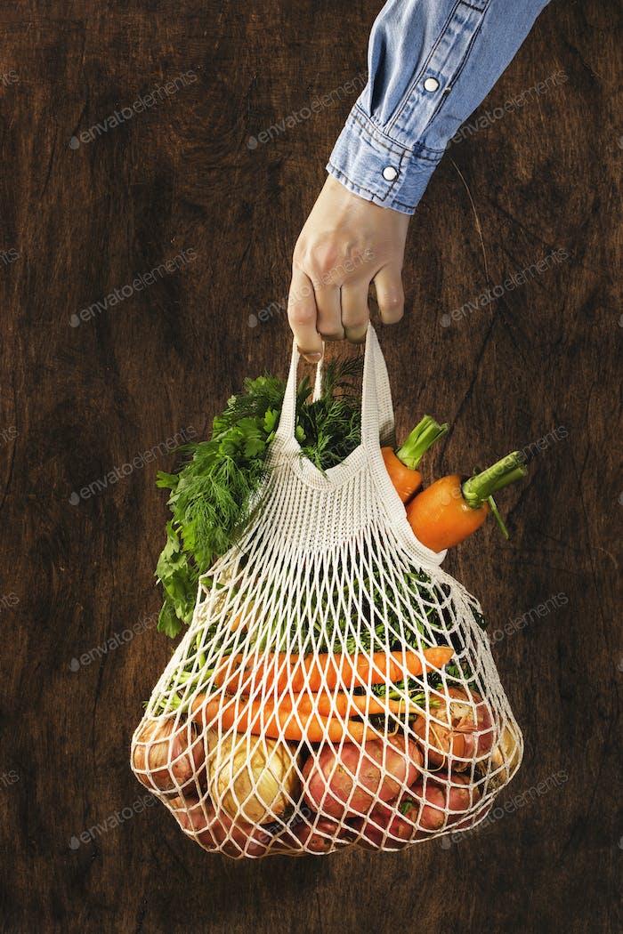 Meshbeutel mit Gemüse und Kräutern in der weiblichen Hand
