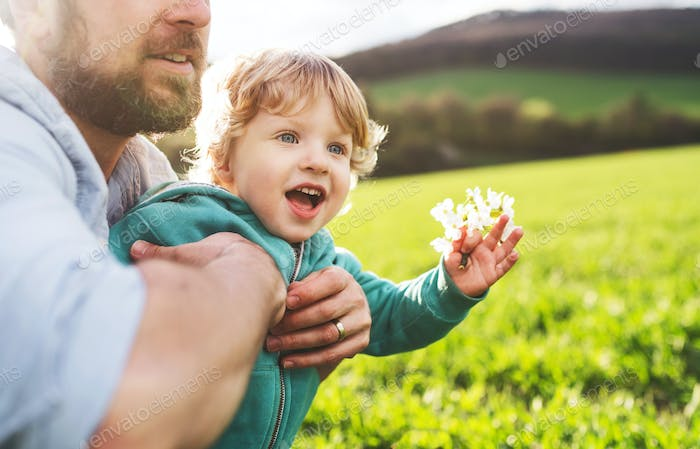 A father with his toddler son outside in spring nature.