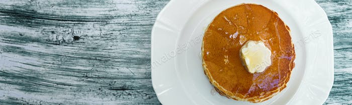 Banner of Top view of pancakes with butter and honey or maple syrup on white plate