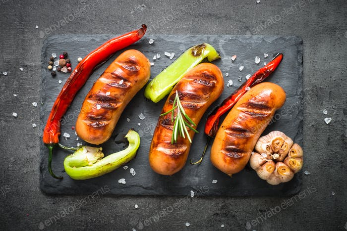 Fried bbq sausages with  vegetables at black background