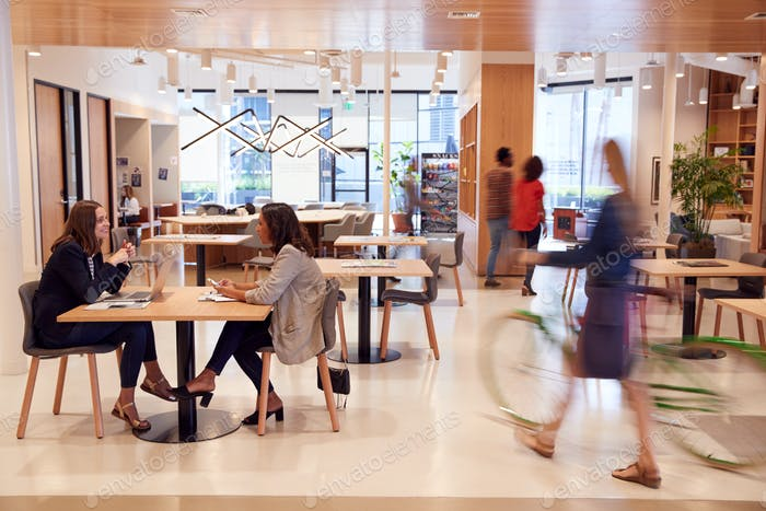 Interior Of Modern Open Plan Office With People Working And Commuters Arriving On Bikes