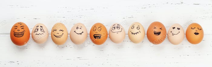 Many eggs with funny faces on wooden table