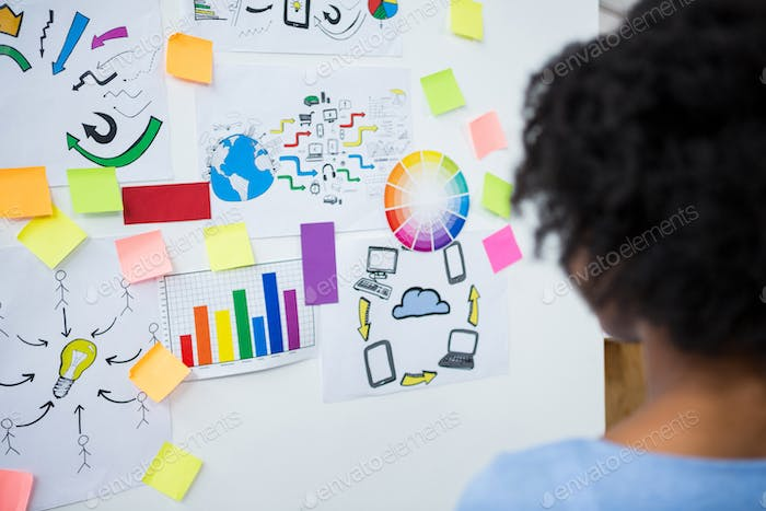 Female graphic designer looking at white board