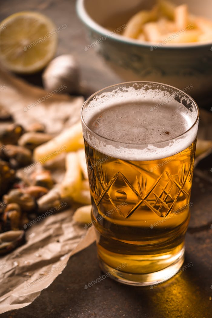 Glass of beer with blurred snack on the metal background