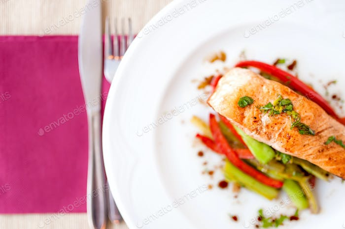 grilled smoked salmon fillet close-up with vegetables and sauce