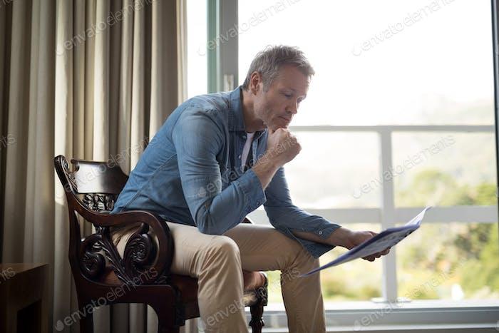 Hombre sentado en la silla y leer el periódico en la sala de estar