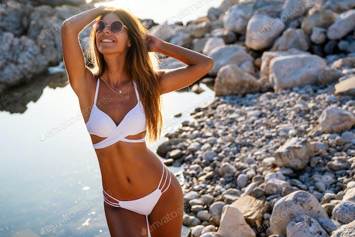Sexy woman in bikini enjoying summer vacation on beach
