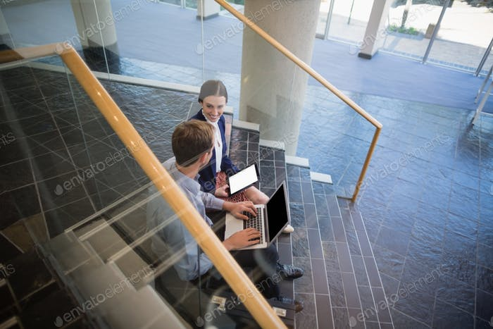 Businessman and woman sitting on steps using laptop and digital tablet