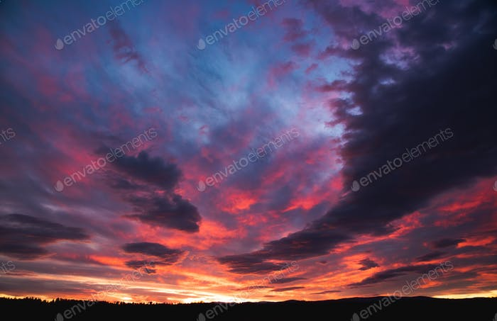 Beautiful dramatic sunset over Styrian land in Austria. Colorful winter evening on countryside