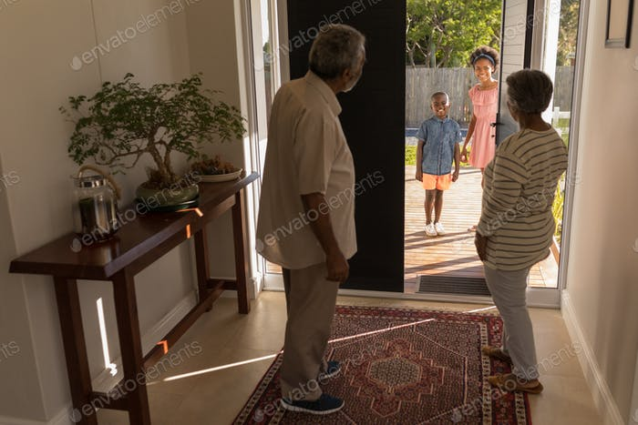 Grandparents standing near door and inviting their grandchildren into their home