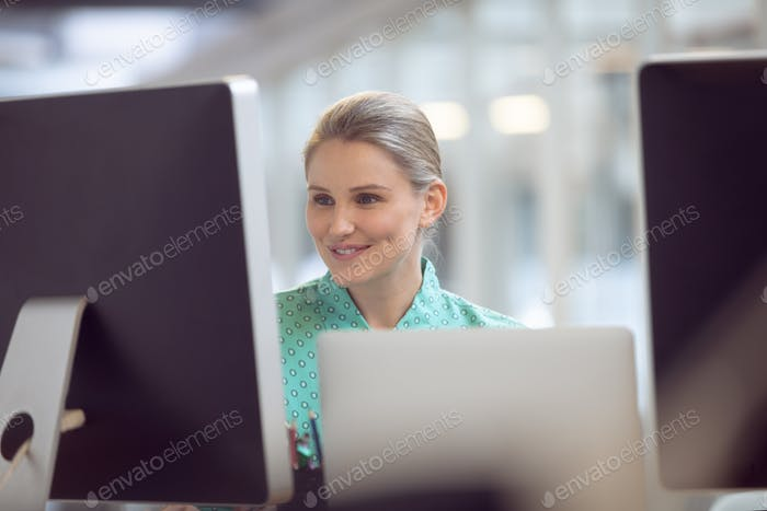 Front view of beautiful Caucasian female executive working on computer at desk in office
