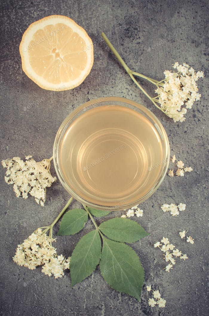 Vintage photo, Fresh healthy juice, elderberry flowers and lemon on structure of concrete